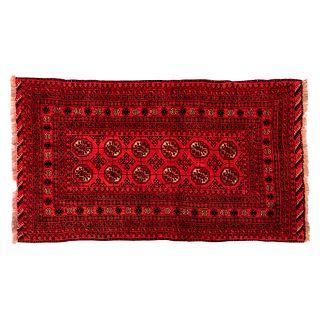 Tapete. Persia. Siglo XX. Estilo Bokhara. Anudado a mano en fibras de lana y algodón. 179 x 103 cm