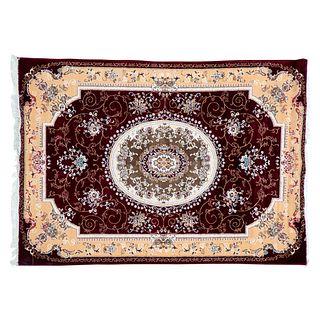 Tapete. Irán, siglo XX. Estilo Mashad. Elaborado en fibras de lana y algodón. Decorado con medallón central sobre fondo vino.