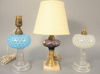 """Three glass oil lamps to include blue opalescent glass oil lamp on clear base, white opalescent oil lamp and amethyst oil lamp, hts. 10"""", 21"""" and 15""""."""