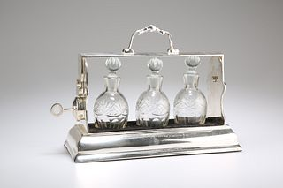 AN EDWARDIAN SILVER-PLATED THREE-BOTTLE TANTALUS, the locking mechanism com