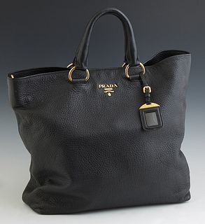 Prada Vitello Diano Black Leather Satchel, c. 2013, with a gold tone snap enclosure opening to a black logo jacquard lining with dua...