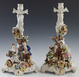 Pair of Meissen Style Porcelain Candlesticks, late 19th/early 20th c., encrusted with flowers, one with a musician and a farmer woman with a goat; the