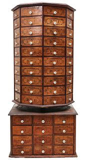 A MONUMENTAL TWO-TIER REVOLVING NUT AND BOLT CABINET