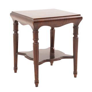 Mesa auxiliar. Siglo XX. Elaborada en madera tallada. Cubierta cuadrangular y chambrana a manera de entrepaño. 76 x 65 x 65 cm