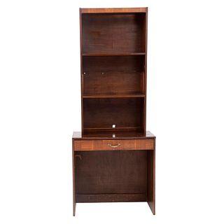Librero. Siglo XX. Elaborado en madera. A 2 cuerpos. Con repisas superiores, cajón con tirador de metal y soportes tipo zócalo.