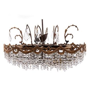 Lámpara de techo. Siglo XX. Diseño oval. Elaborado en metal dorado. Para 14 luces. Decorado cuentas y almendrones facetados de cristal.