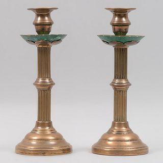 Par de candeleros. Siglo XX. Elaborados en cobre dorado. Con arandelas de malaquita, fustes arquitectónicos y soportes circulares.