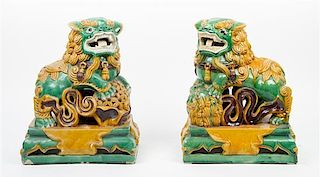 * A Pair of Sancai Pottery Fu Lions Height 15 1/4 x width 12 1/4 inches.