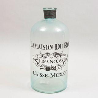 Botella. Diseñada para parecerse a un antiguo recipiente de vino francés. Elaborada en vidrio. Con inscripción.