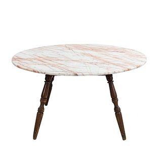 Mesa de centro. Siglo XX. En talla de madera. Con cubierta circular de mármol rosado jaspeado. 75 x 140 cm Ø