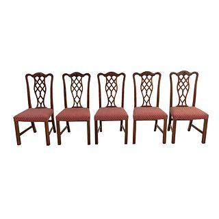 Lote de 5 sillas. Siglo XX. Estilo Jorge III. En talla de madera. Con respaldos semiabiertos y asientos en tapicería color bermellón.