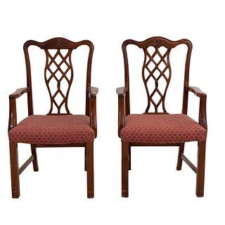Par de sillones. Siglo XX. Estilo Jorge III. En talla de madera. Con respaldos semiabiertos y asientos en tapicería color bermellón.