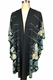 Black, turquoise and pale green ruana with leaves and butterflies.