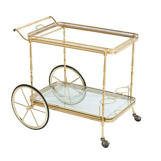 Carrito de servicio. Siglo XX. Elaborado en metal dorado. A 2 niveles. Con cubierta inferior de vidrio con ribete de espejo.