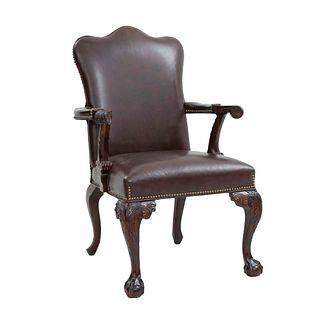 Sillón. Siglo XX. Estilo inglés. En talla de madera. Con respaldo cerrado y asiento de piel color marrón.