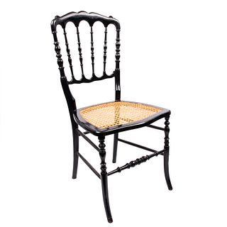 Silla. Siglo XX. Estilo victoriano. Elaborada en madera ebonizada con asiento de bejuco. Respaldo semiabierto, fustes torneados.