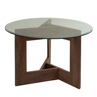 Mesa. Siglo XX. Estilo moderno En madera con recubrimiento vinilico tipo nogal. Con cubierta circular de vidrio. 77 x 120 cm