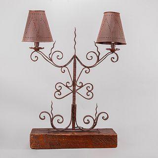 Lámpara de mesa. Siglo XX. Estructura de metal forjado con base de madera rústica. Para 2 luces. Decorada con roleos.