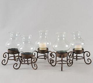 Lote de 5 candeleros. Siglo XX. Elaborados en hierro. Con pantallas de vidrio y soportes a manera de roleos.