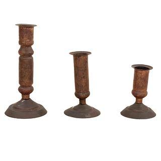Lote de 3 candeleros. Siglo XX. Elaborados en cobre. Con arandelas circulares, fustes compuestos y soportes circulares.