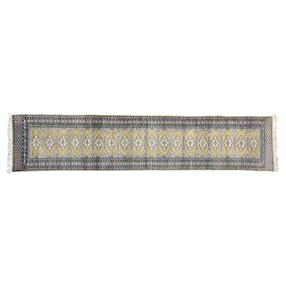 Tapete de pasillo. Siglo XX. Estilo Bokhara. Elaborado en fibras de lana y algodón. Decorado con motivos geométricos.