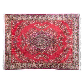 Tapete. Siglo XX. Estilo Mashad. Elaborado en fibras de lana y algodón. Decorado con medallón central sobre fondo carmín.