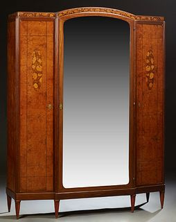 French Inlaid Walnut Armoire, c. 1930, the arched crest over an arched beveled mirror door, flanked by setback narrow doors, on a pl...