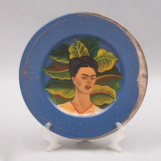 """Emilia Castillo. Plato """"Frida Kahlo"""". Firmado y fechado 03. En cerámica azul con aplicaciones de plata baja, pintado a mano."""