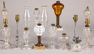 Eleven glass fluid and table lamps.