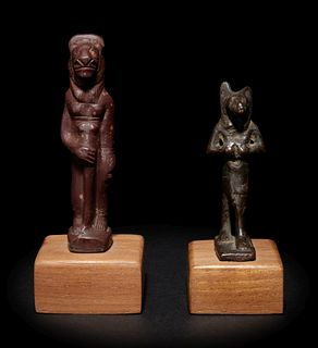 An Egyptian Stone Striding Bastet and an Egyptian Bronze Anubis  Height of taller example 3 1/8 inches; height of shorter example 2 1/8 inches.