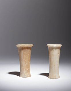 Two Egyptian Alabaster Columnar Vessels Height of taller example 4 1/2 inches; height of shorter example 4 3/8 inches.