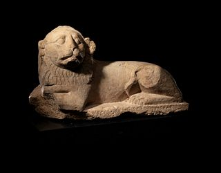 An Egyptian Limestone Recumbent Lion Height 10 3/4 x width 18 inches.