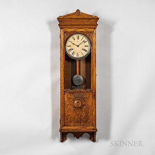 Bundy Time Recorder Wall Clock, Binghamton, New York, oak case with full-length door, upper portion glazed, lower wood panel with folia