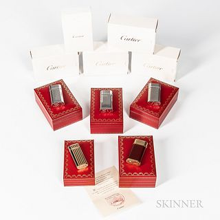 "Five Cartier ""Briquets"" Lighters, all with original inner and outer boxes and paperwork, including a ""Miniature Briquet"" in a gold and"