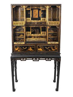 A Chinese Export Gilt Decorated Black Lacquered Cabinet-on-Stand Height 72 x width 38 1/2 x depth 19 inches.