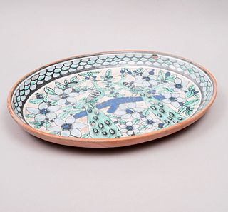 Centro de mesa. México, siglo XX. Diseño oval. Elaborado en mayólica policromada y vidriada. Decorado con pavorreales y otros.