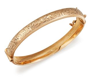A 9CT GOLD BANGLE, the hinged bangle with bright cut engrav