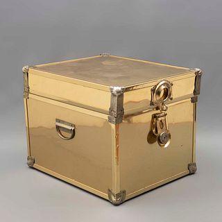 Baúl. SXX. Elaborada en aglomerado con recubrimiento de lámina de metal dorado. Con cubierta abatible, cerrojo y asas. 33 x 36 x 44 cm