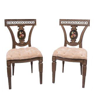 Par de sillas. Siglo XX. Estructura de madera. Con respaldos semiabiertos y asientos capitonados. Piezas: 2.