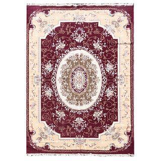 Tapete. Siglo XX. Estilo mashad. Elaborado en fibras de lana y algodón. Decorado con motivos orgánicos, florales y medallón.