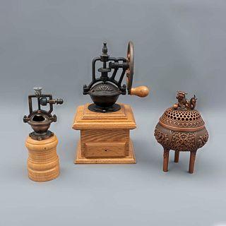 Lote de 3 piezas. Siglo XX. Elaboradas en metal, hierro y madera. Consta de: incensario y 2 molinos. Uno con cajón y manivela.