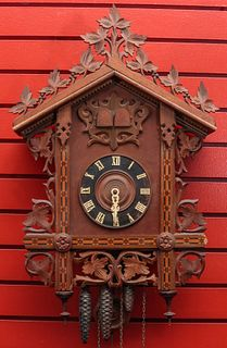AN EARLY 20TH C. CUCKOO CLOCK WITH CARVING AND INLAY