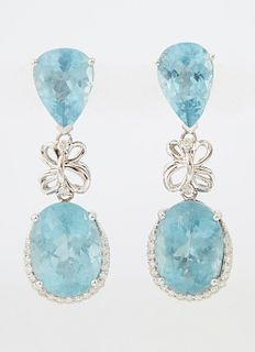 Pair of 14K White Gold Pendant Earrings, each with a pear shaped aquamarine stud suspending a diamond mounted bow bail atop an oval...