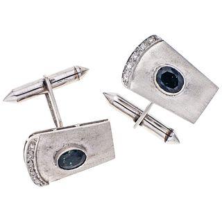 Par de mancuernillas con zafiros y diamantes en plata paladio. Peso: 12.6 g  2 Zafiros corte oval facetado ~0.70 ct  10 Diamantes.