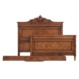 Cama. Francia. Siglo XX. En talla de madera de nogal. Con cabecera, piecera, largueros y soportes tipo carrete.