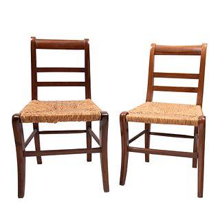 Par de sillas. Siglo XX. En talla de madera. Con respaldos escalonados, asientos de palma y chambrana en caja.