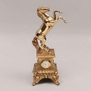 Reloj de mesa. Siglo XX. Elaborado en metal dorado. Mecanismo de cuarzo. Carátula circular, índices romanos y manecillas tipo espada.