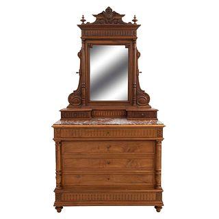 Tocador. Francia. Siglo XX. En talla de madera de nogal. A 2 cuerpos. Con espejo de luna rectangular biselada.