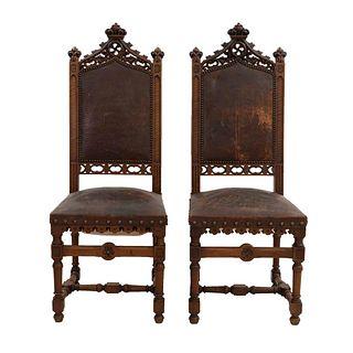 Par de sillas. Francia. Siglo XX. Estilo Enrique II. En talla de madera de nogal. Con respaldos semiabiertos.
