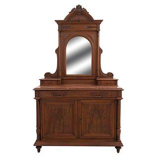 Tocador. Francia. Siglo XX. Estilo Enrique II. En talla de madera de nogal. A 2 cuerpos. Con espejo de luna irregular.